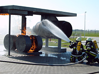 Die Fahrwerk-Attrappe brennt. Die Löschmänner lenken den Wasserstrahl auf den Flügel des Flugzeuges, damit dieser nicht schmilzt.